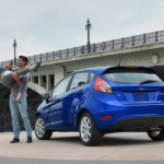 A young coupe is taking a selfie in front of their blue 2019 Ford Fiesta that they got with Ford lease deals in Cincinnati, OH.