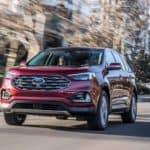 A red 2019 Ford Edge, one of the popular Ford SUVs in Cincinnati, OH, is driving in front of city buildings.