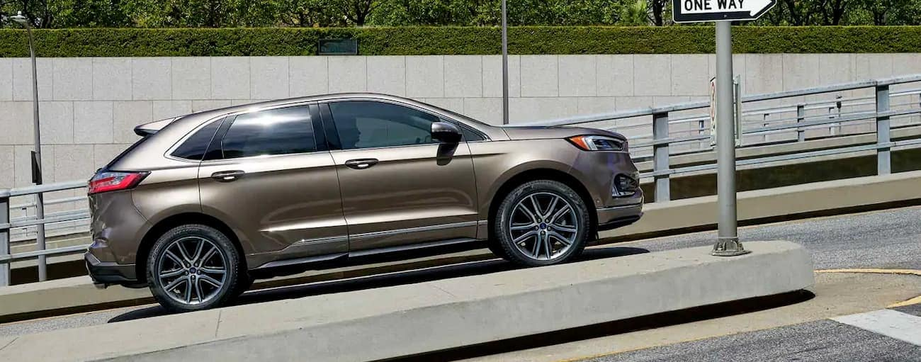 A gold 2019 Ford Edge is stopped at an intersection on a hill in Cincinnati, OH.