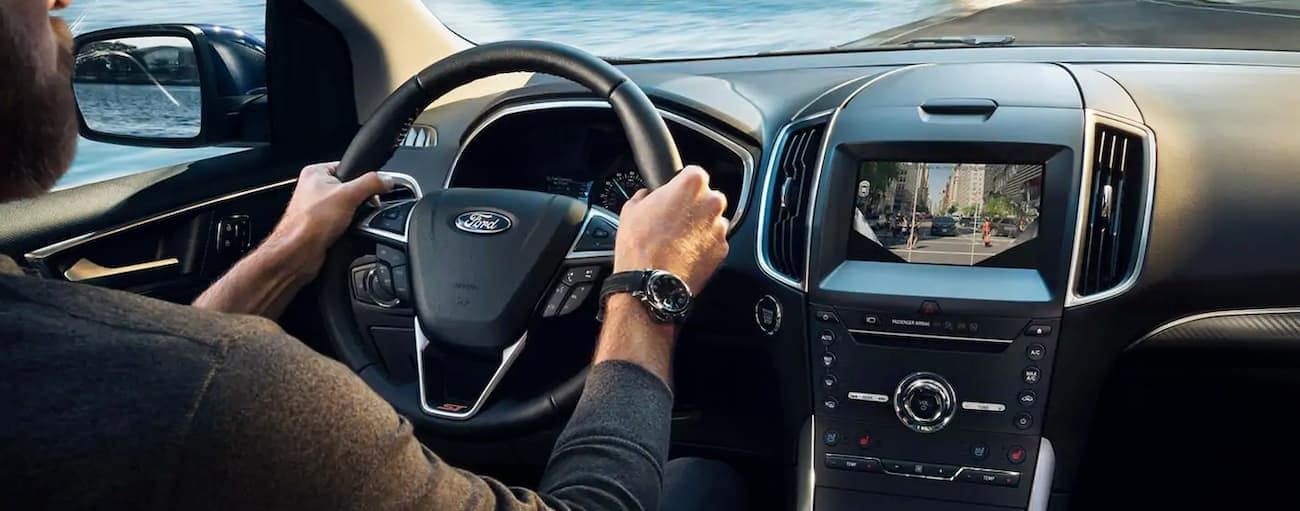 The interior of a 2019 Ford Edge is shown as the driver passes a lake outside Cincinnati, OH.