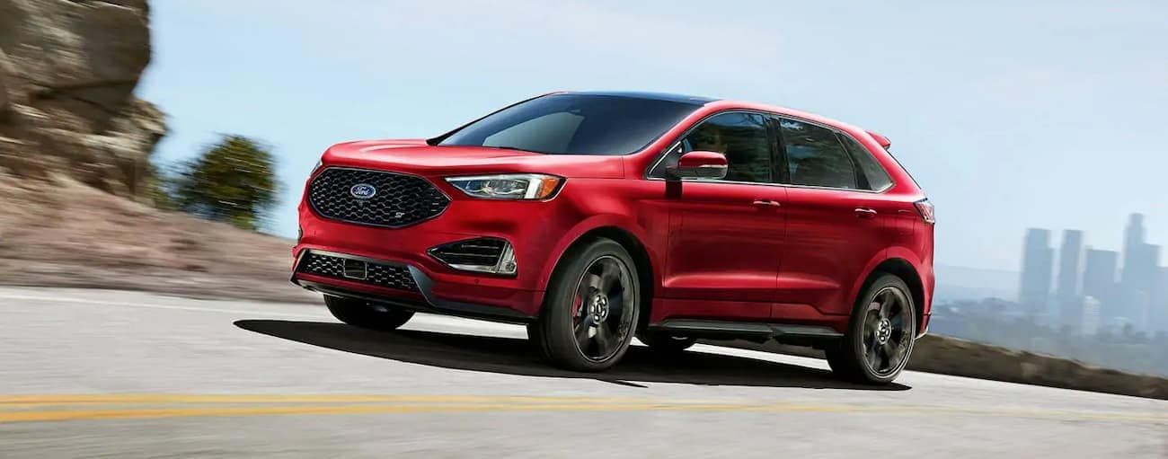 A red 2019 Ford Edge, which wins when comparing the 2019 Ford Edge vs 2019 Jeep Cherokee, is taking a corner with buildings in the background.