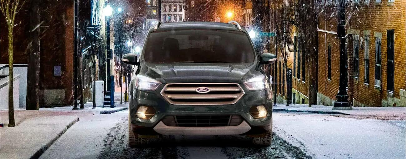 A green 2019 Ford Escape, whose capability wins when comparing the 2019 Ford Escape vs 2019 Hyundai Tucson in Cincinnati, OH, is driving uphill in the snow at night.