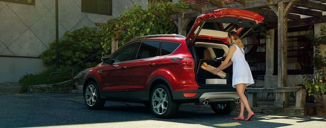 A woman is loading things into the back of her red 2019 Ford Escape in Cincinnati, OH.