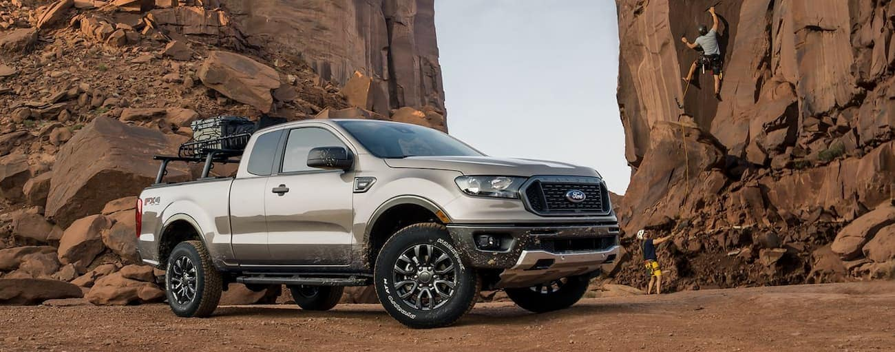 A tan 2019 Ford Ranger is parked between cliffs while the owners rock climb.