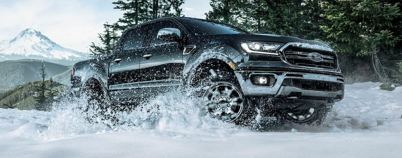 A black 2019 Ford Ranger is driving in the snow in front of mountains.