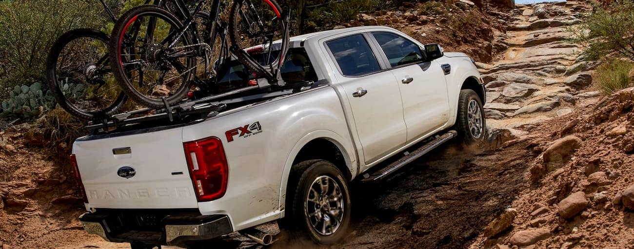 A white 2019 Ford Ranger, which wins when comparing towing and payload for the 2019 Ford Ranger vs 2019 Honda Ridgeline, is on a trail with bikes in the bed.