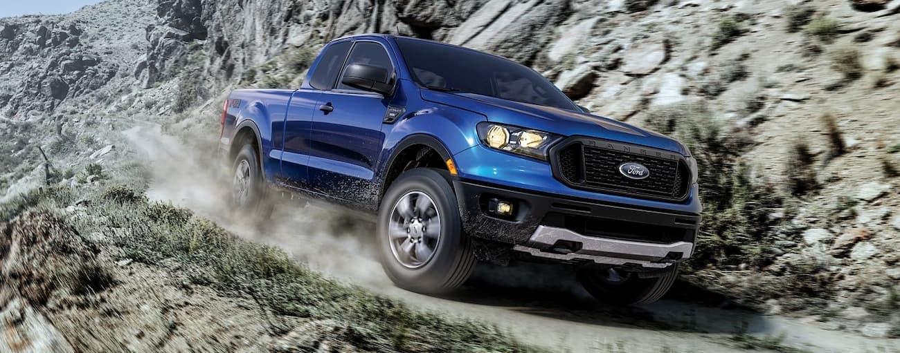 A blue 2019 Ford Ranger is taking a corner on a rocky cliff trail.