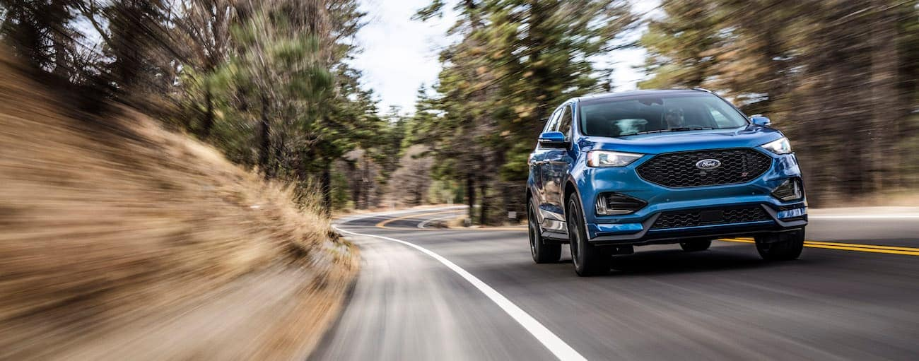 A blue 2019 Ford Edge, which wins when comparing the  2019 Ford Edge vs 2019 Dodge Journey, is driving along a tree-lined road.