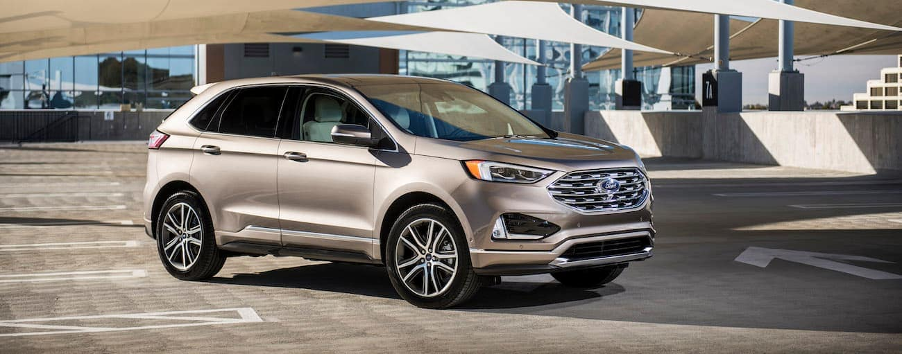 A tan 2019 Ford Edge is parked under cover near a glass building.