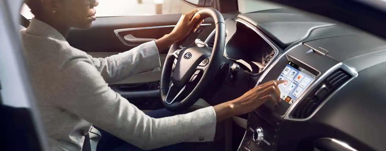 A woman is using the touchscreen in her 2019 Ford Edge to get around Cincinnati, OH.