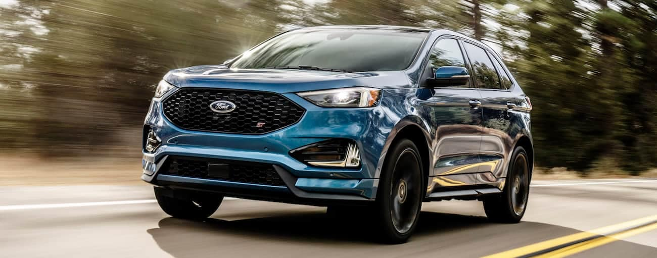A blue 2019 Ford Edge ST, which wins when comparing the 2019 Ford Edge vs 2019 Honda Passport, is driving on a tree-lined road.