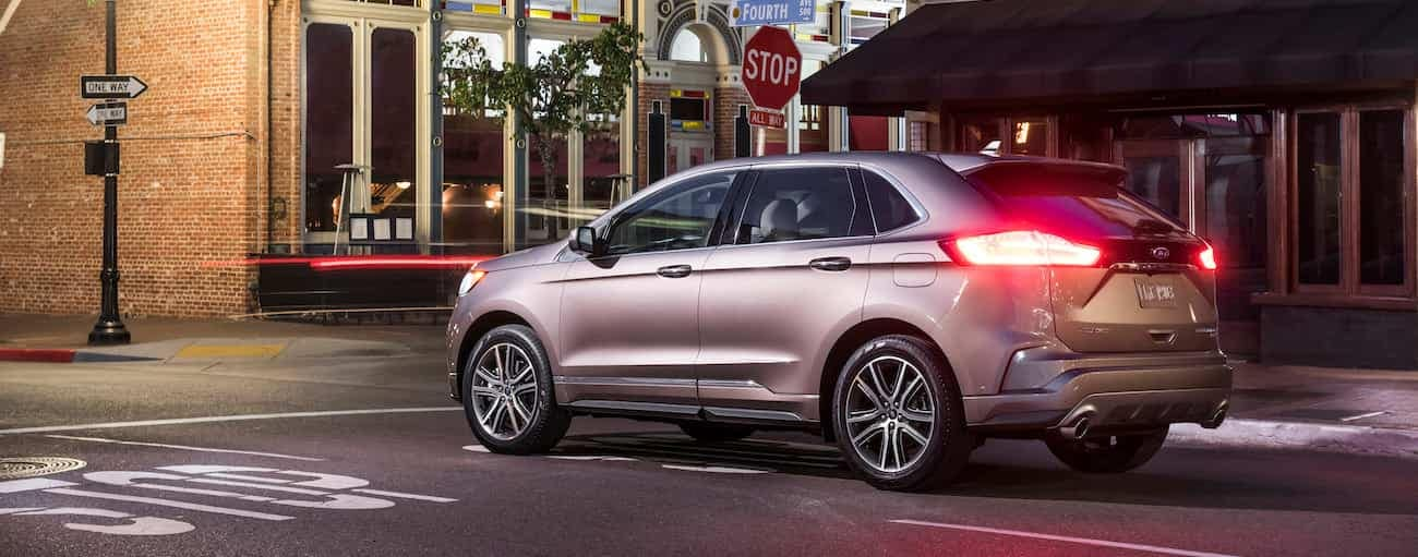 A tan 2019 Ford Edge is at an intersection near Cincinnati, OH at night.