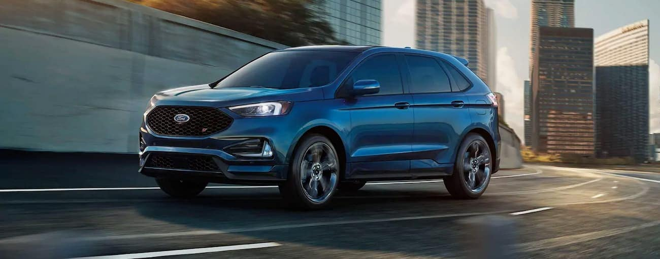 A blue 2019 Ford Edge, which wins when comparing performance for the 2019 Ford Edge vs 2019 Kia Sorento, is rounding a corner in Cincinnati, OH.