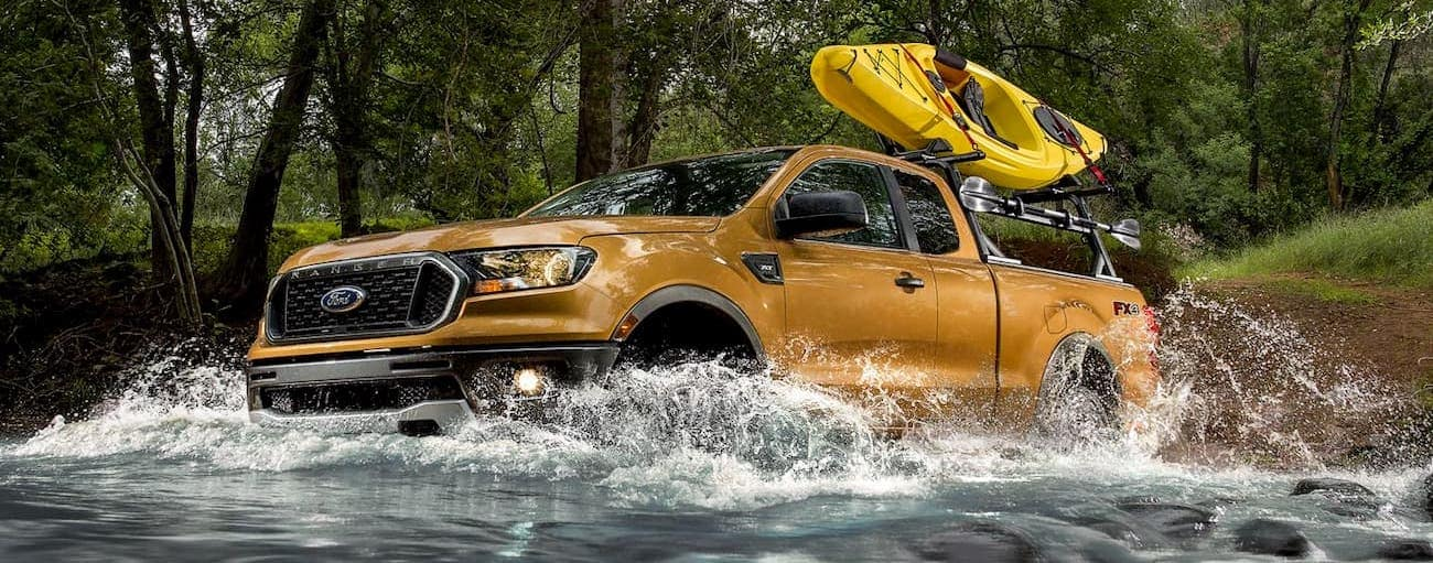 A gold 2019 Ford Ranger is crossing through a river with a kayak on the roof while on vacation from Cincinnati, OH.