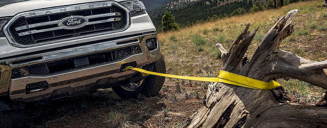 A white 2019 Ford Ranger has a strap connected from the tow hook to a stump.