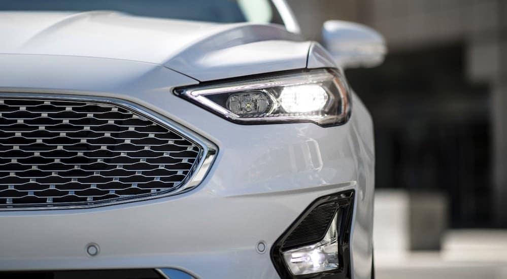 The front end of a white 2019 Ford Fusion, which is popular among Ford cars for sale, is shown.