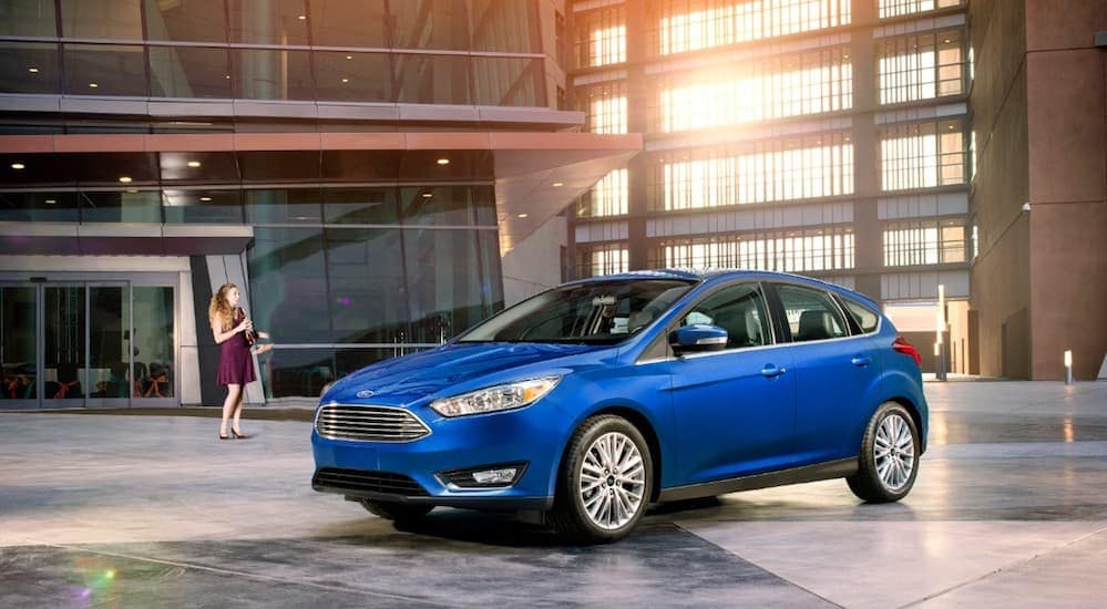 A blue 2018 Ford Focus is parked in front of an office building with a women smiling at it.
