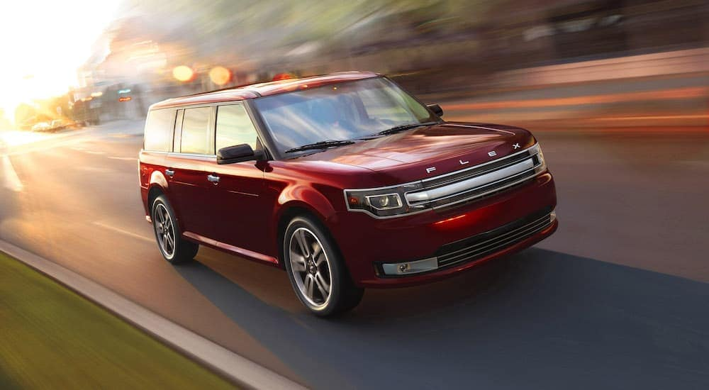 A red 2016 Ford Flex is driving with a blurry background.