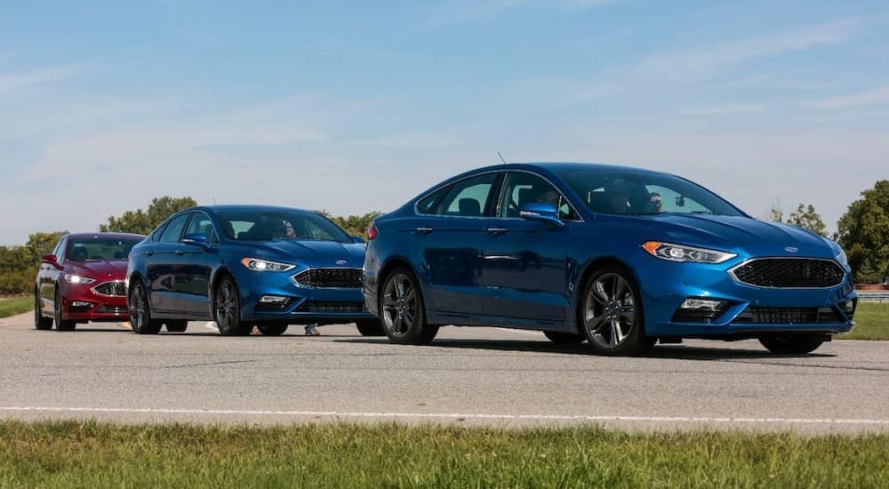 Three 2017 Ford Fusions, popular used cars in Cincinnati, are lined up on a track.