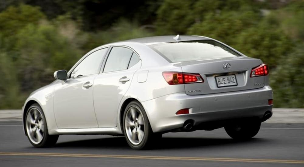 A silver 2009 Lexus IS, a popular choice for used cars priced under 10k, is driving on a paved road outside Cincinnati, OH.