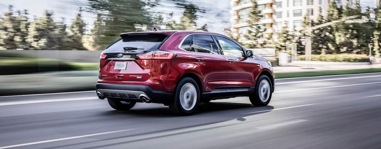 A red 2019 Ford Edge, which wins when comparing the 2019 Ford Edge vs 2019 Nissan Murano, is driving towards tall buildings.