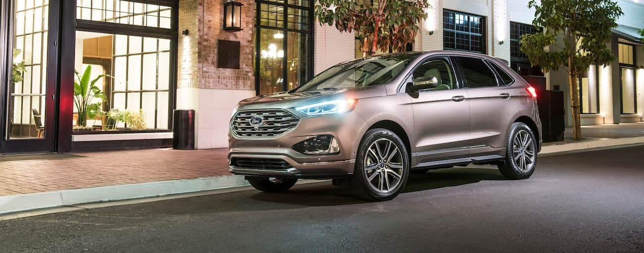 A tan 2019 Ford Edge is parked downtown in Cincinnati, OH at night.