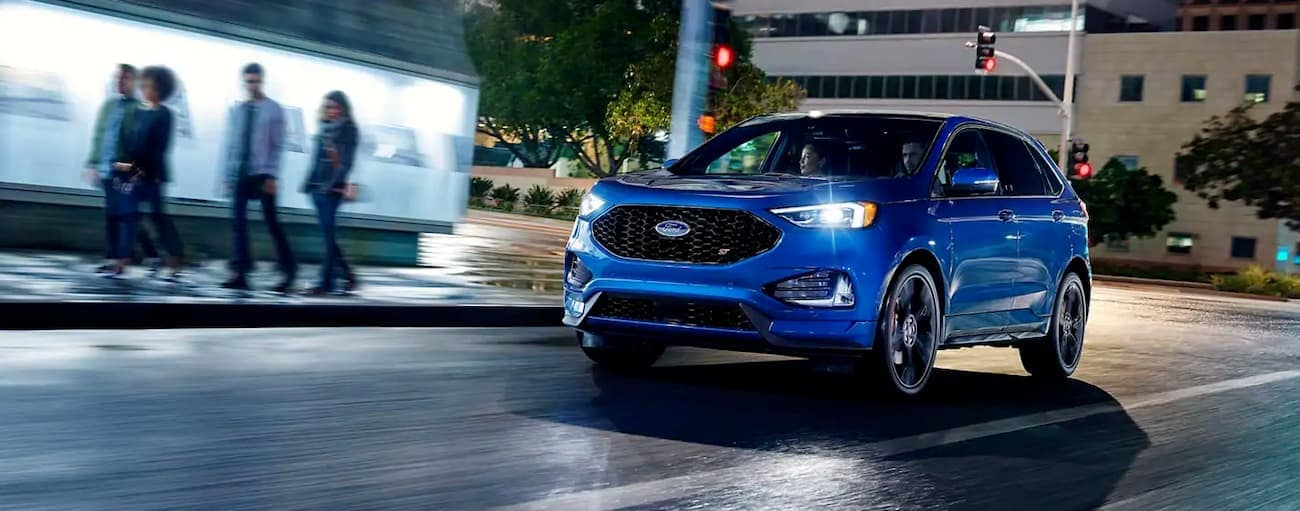 A blue 2019 Ford Edge, which wins when comparing the 2019 Ford Edge vs. 2019 Chevy Blazer, is in a city at night.