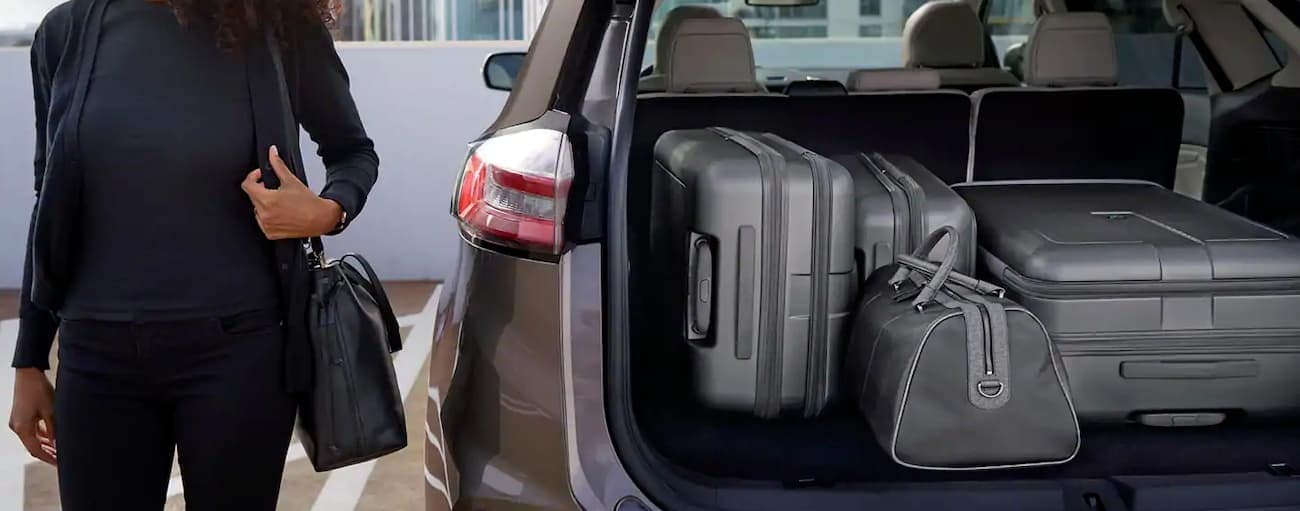 A woman is next to her 2019 Ford Edge with the trunk open and full of luggage.