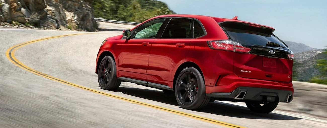 A red 2019 Ford Edge is driving up hill.