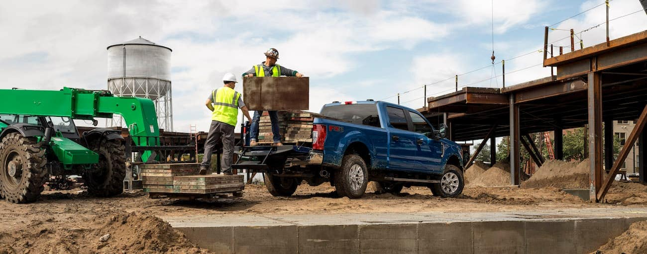 Workers are loading a blue 2020 Super Duty Ford F-250 at a construction site.