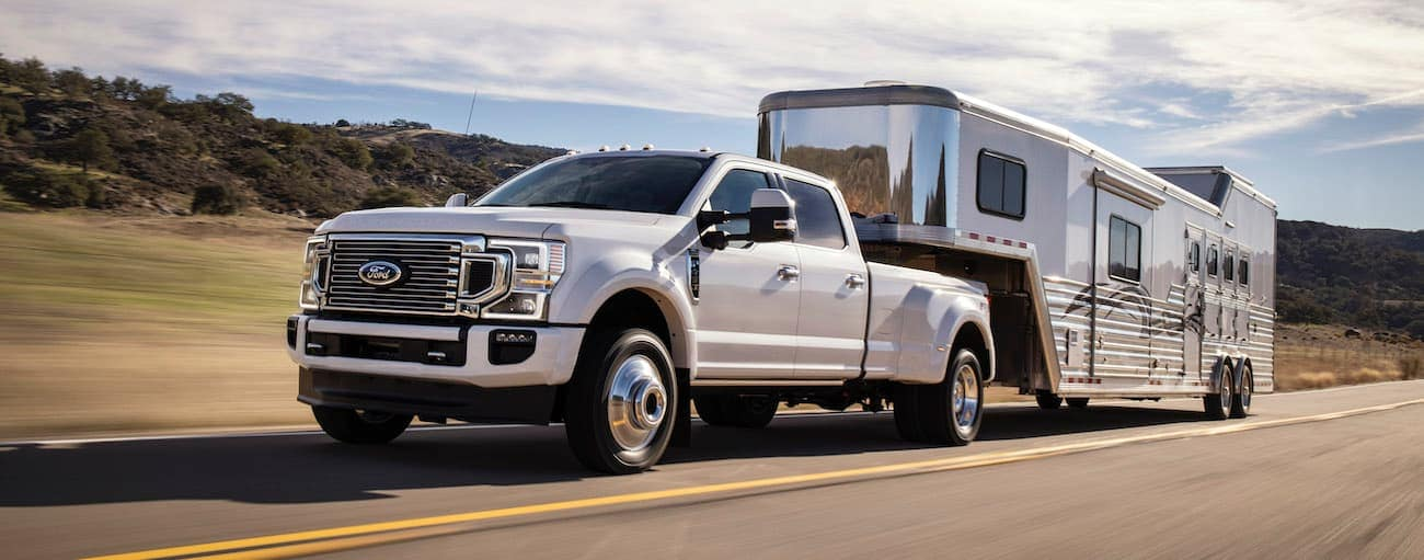 A white 2020 Super Duty Ford F-450 is towing a trailer.