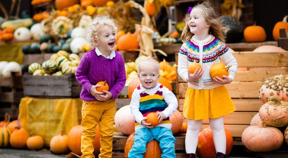 Three kids are at a pumpkin stand.