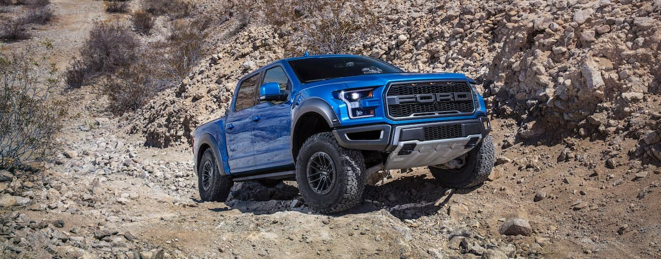 A blue 2019 Ford Raptor is on a rocky trail in the desert.