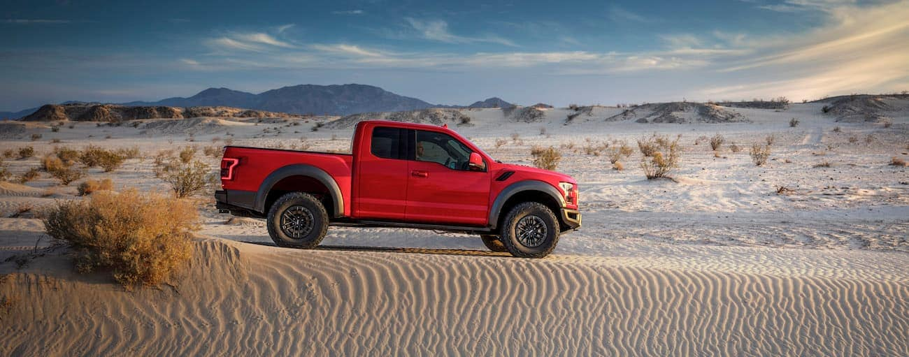A red 2019 Ford Raptor is in the sand in a desert.