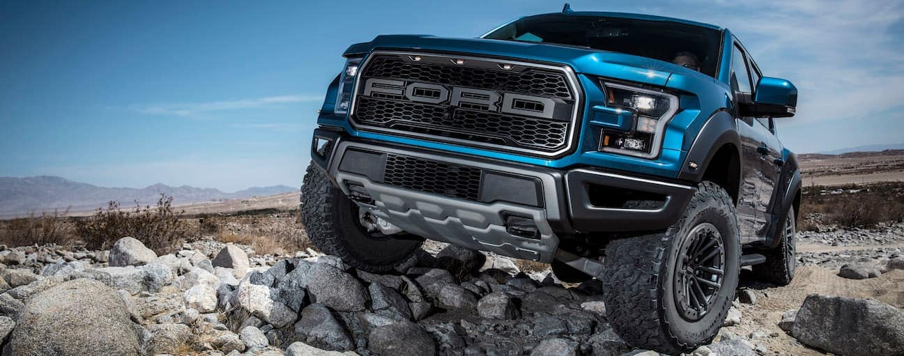A 2019 Ford Raptor, which wins when comparing the 2019 Ford Raptor vs Chevy Trail Boss, is rock crawling up a hill.