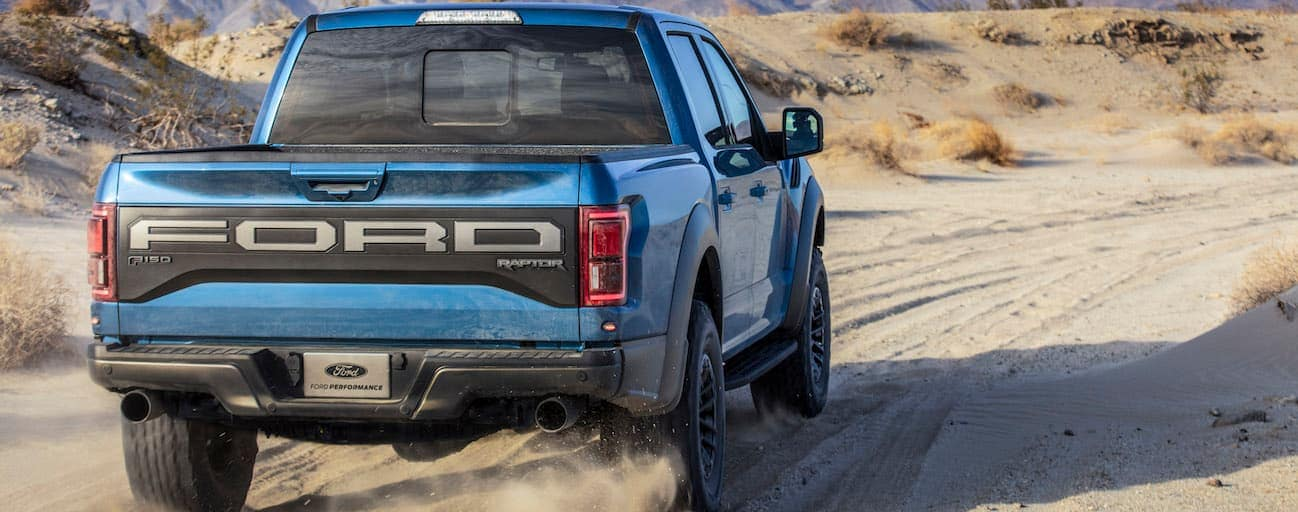 A blue 2019 Ford Raptor is driving down a desert road.