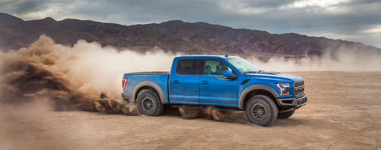 A blue 2019 Ford Raptor is driving through the desert.