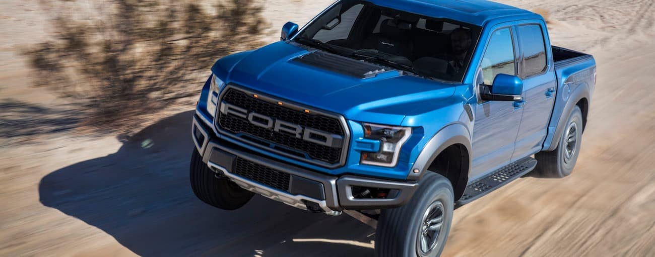 A blue 2019 Ford Raptor, which wins when comparing the 2019 Ford Raptor vs 2019 Ram Rebel, is racing down a desert road.
