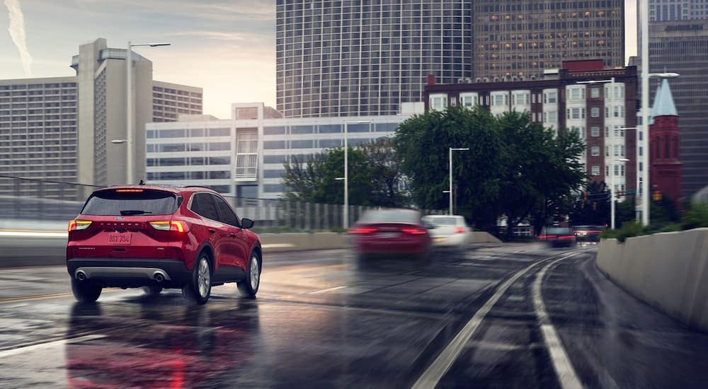 A red 2020 Ford Escape is on a city highway in the rain.