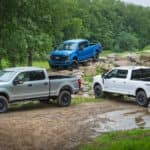 Three of the 2020 Ford Super Duty trucks are parked on a muddy trail off-road.