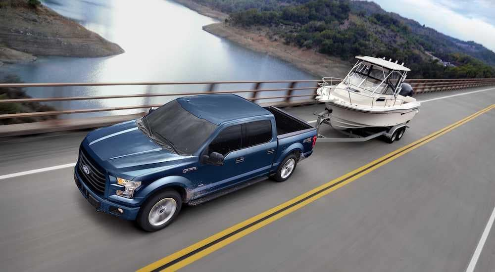 A blue 2017 Ford F-150, popular among used Ford trucks, is towing a boat.