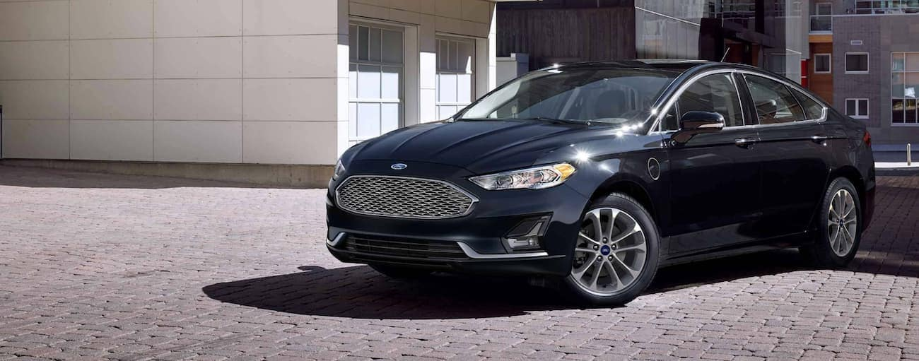 A black 2019 Ford Fusion, which wins when comparing the 2019 Ford Fusion vs 2019 Kia Optima, is parked in front of concrete buildings.