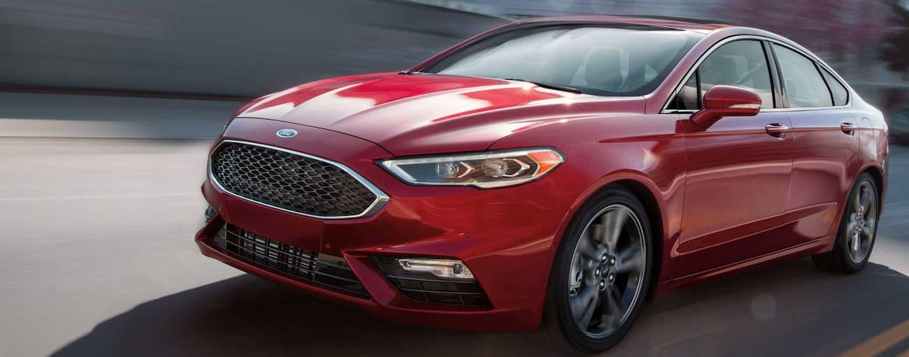 A red 2019 Ford Fusion is driving on a highway.