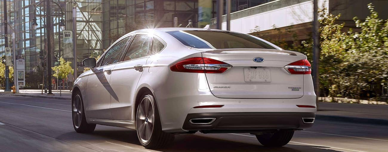 A white 2019 Ford Fusion is driving on a city street near Cinicnnati, OH.