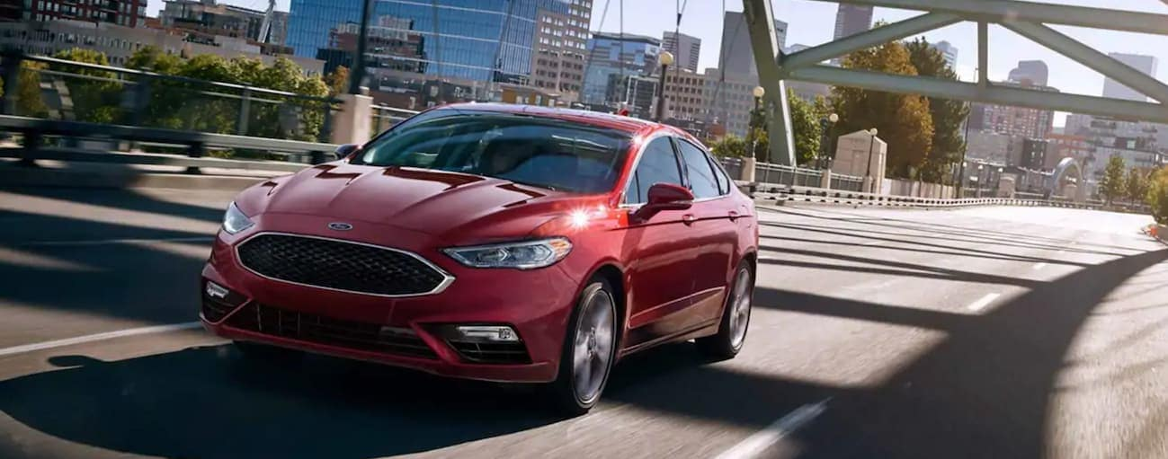 A red 2019 Ford Fusion, which wins when comparing the 2019 Ford Fusion vs 2019 Toyota Camry, is driving on a bridge near Cincinnati, OH.