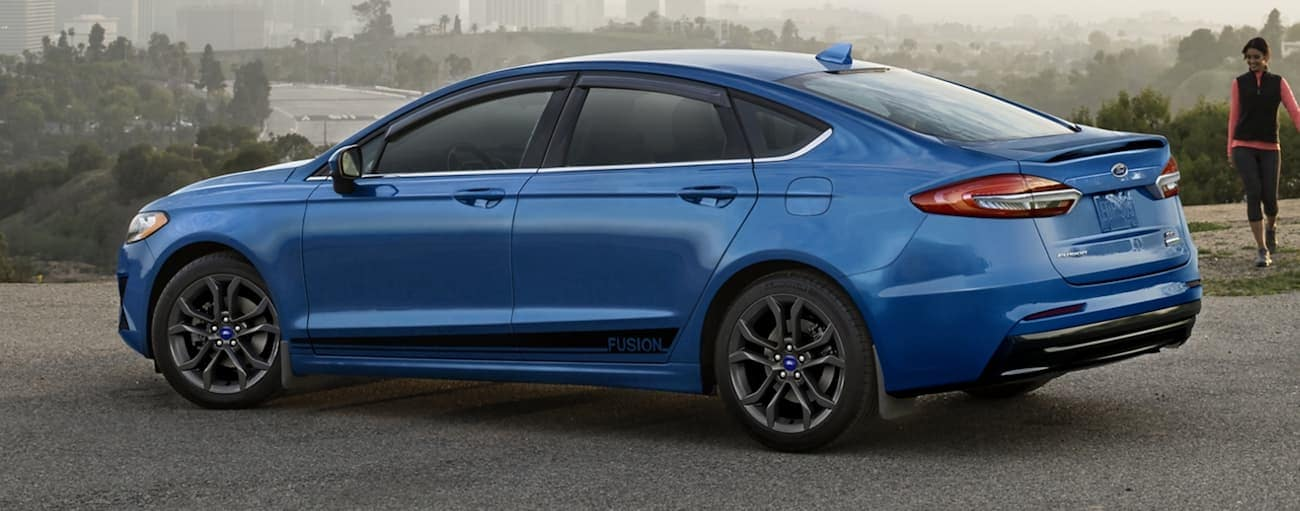A blue 2020 Ford Fusion is parked with a city in the distance.