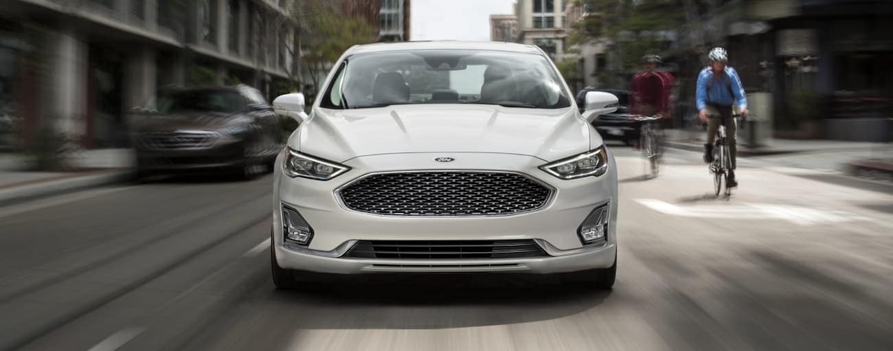 Cyclists are riding up next to a white 2020 Ford Fusion on a city street.