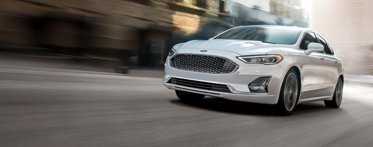 A white 2020 Ford Fusion is driving quickly down a road in Cincinnati, OH.