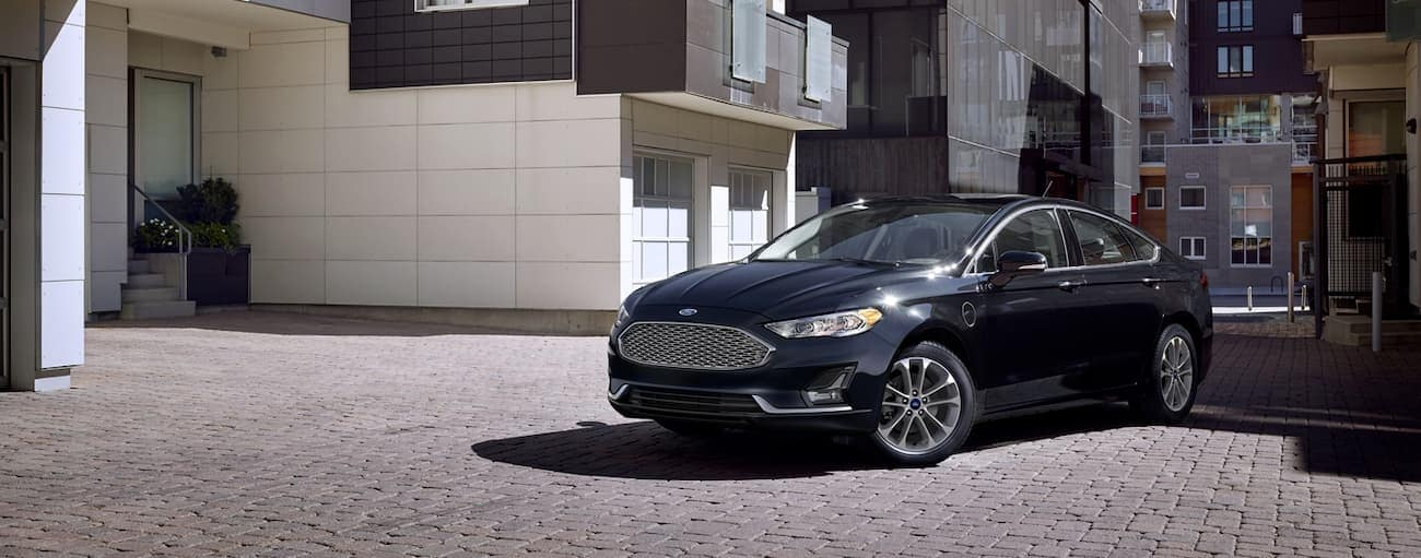 A black 2020 Ford Fusion is parked outside Cincinnati, OH townhouses and apartments.