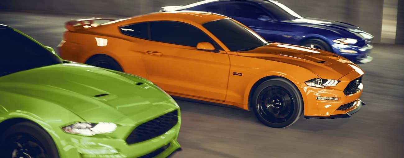 Three 2020 Ford Mustangs in green, orange, and blue are racing.